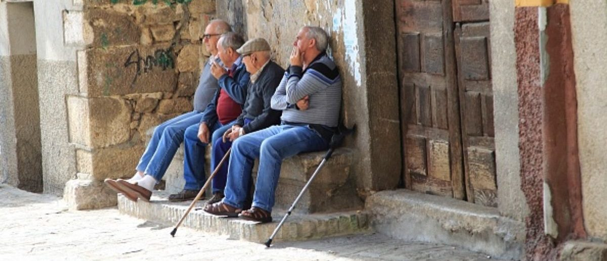 Men sitting together on stone bench, Garganta la Olla, La Vera, Extremadura, Spain. (Photo by: Geography Photos/UIG via Getty Images) | Man Legally Changes Gender To Retire
