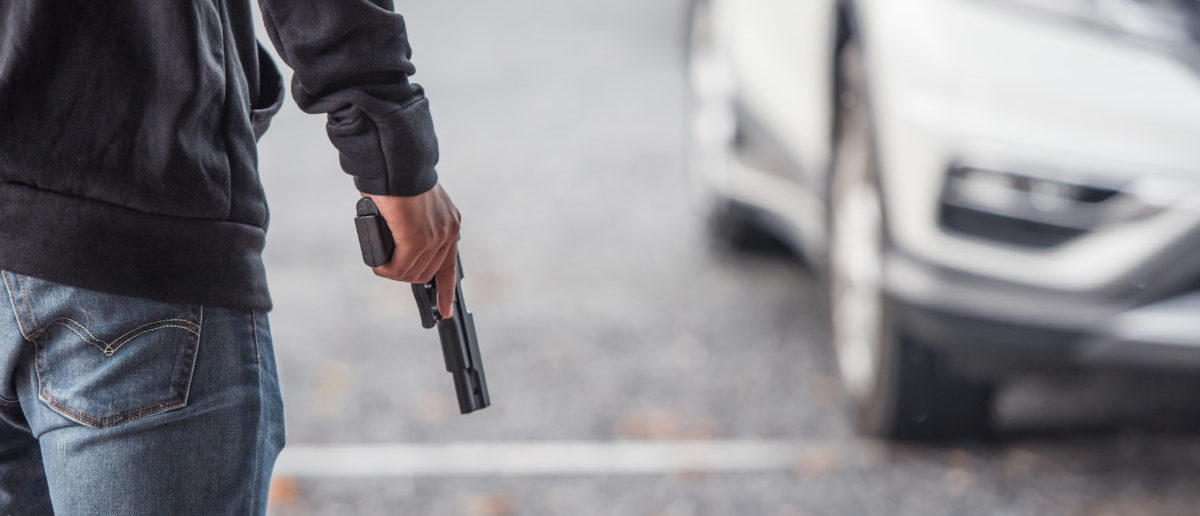 Back view of man holding a gun in car park -- ShutterStock By May_Chanikran