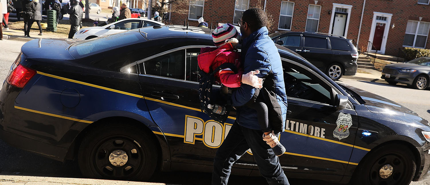 """A man stops to thank the police as activists, residents and those that have lost a loved one to violence participate in a """"Peace and Healing Walk"""" in an area with a high rate of homicides during Baltimore's third """"Ceasefire Weekend"""" on February 3, 2018 in Baltimore, Maryland. The walk stopped at numerous locations where an individual was recently murdered to say a prayer. Baltimore, one of the poorest major cities in the United States, experienced 341 homicides last year, the highest per-capita rate on record for the city. The third citywide Ceasefire event began on Friday, with organizers and community members calling for peace for a 72-hour period and holding numerous events, including peace walks, movie screenings and a youth basketball tournament among other gatherings. (Photo by Spencer Platt/Getty Images)"""