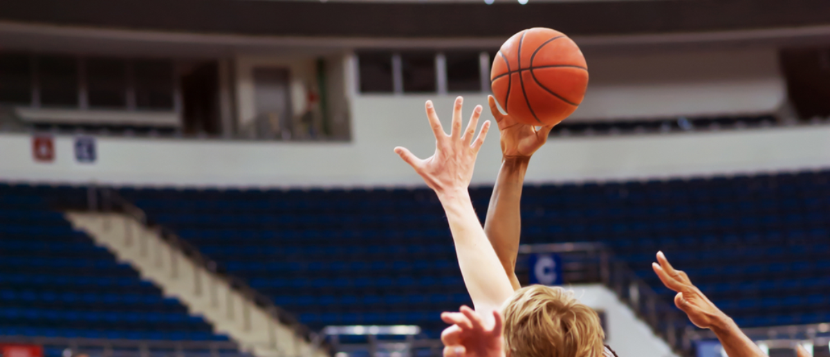 A basketball player's hand throws the ball into the basket (SHUTTERSTOCK: By PhotoProCorp)