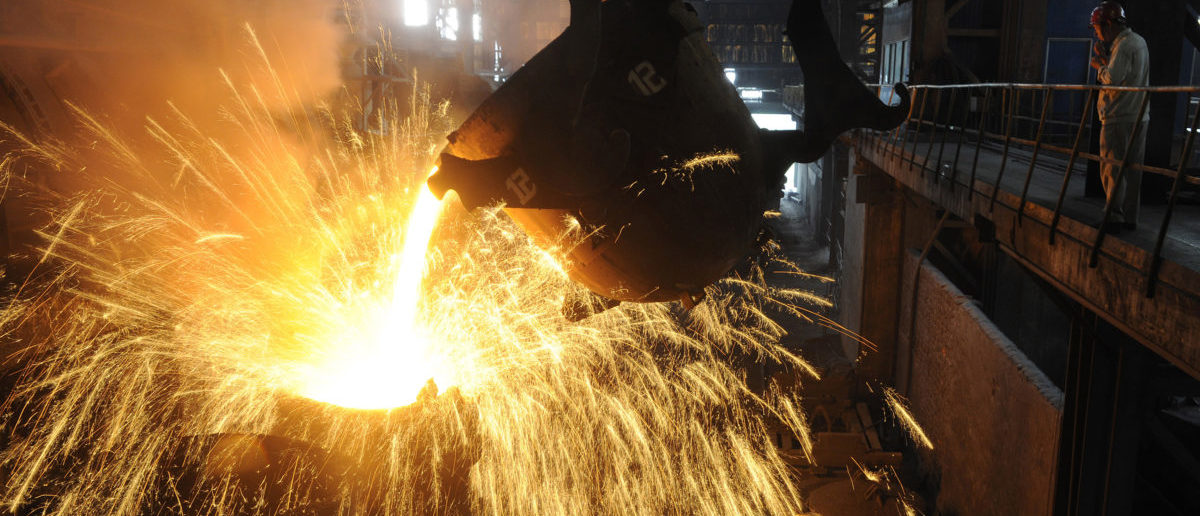 An employee monitors molten iron being poured into a container at a steel plant in Hefei, Anhui province September 9, 2013. China's average daily crude steel output stood almost unchanged at 2.119 million tonnes between Aug. 21-31, compared with 2.118 million tonnes between Aug. 11-20, data from the China Iron & Steel Association showed on Monday. REUTERS/Stringer