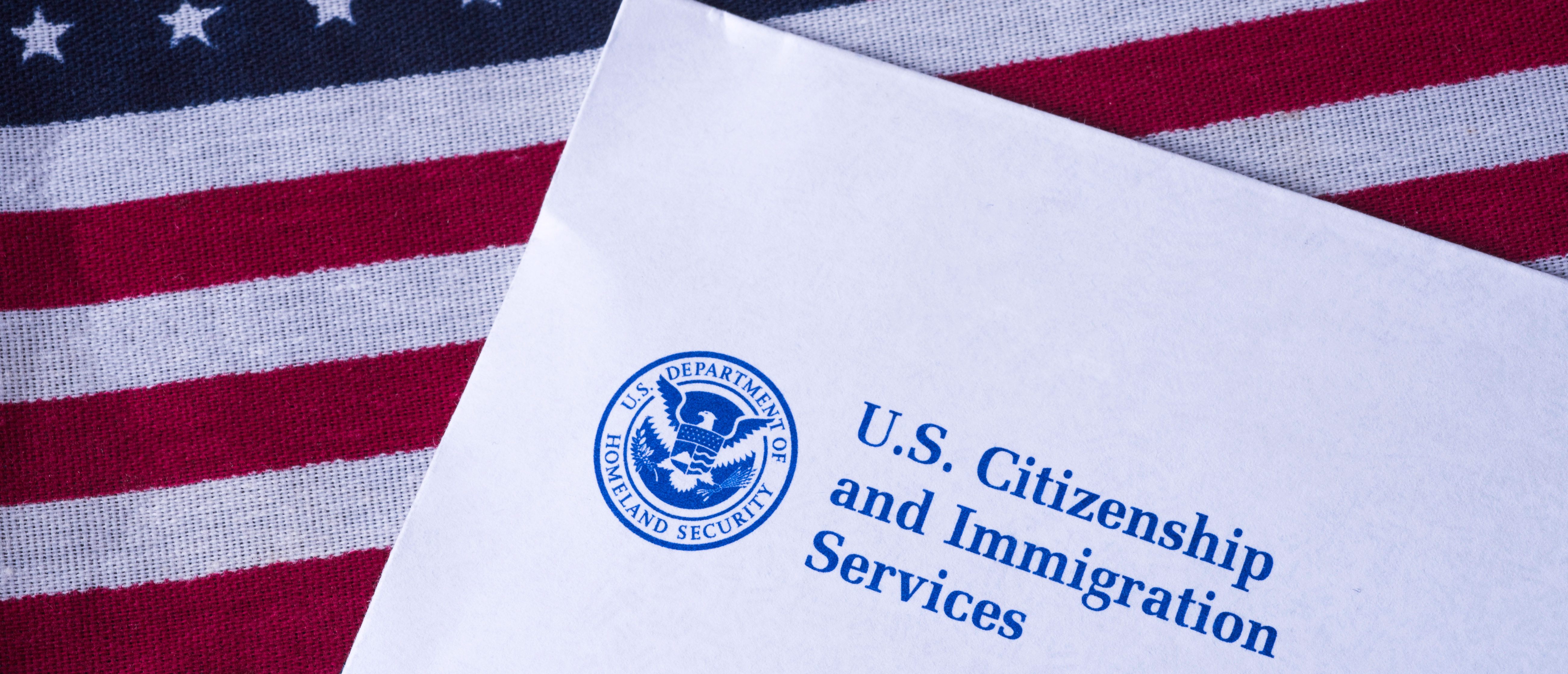 Letter from US Citizenship and Immigration Services on Flag of United States of America. Shutterstock.