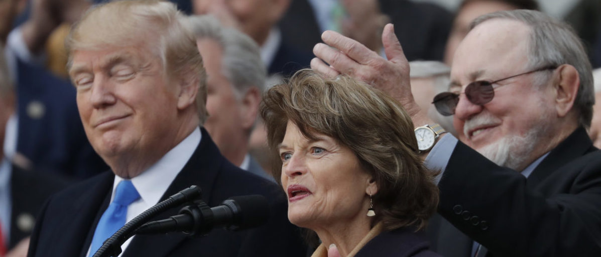 U.S. President Donald Trump stands with with Alaska's Sen. Lisa Murkowski (R-AK), and Rep Don Young (R-AK) as he celebrates with Congressional Republicans after the U.S. Congress passed sweeping tax overhaul legislation on the South Lawn of the White House in Washington, U.S., December 20, 2017. REUTERS/Carlos Barria
