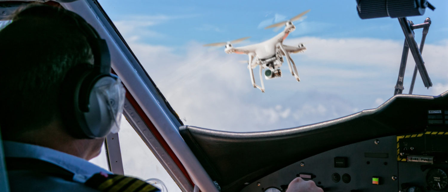 An unmanned aerial vehicle, or drone,  flies into the view of a commercial airline pilot. [Shutterstock - Jag_cz]