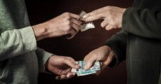 Hand of addict man with money buying dose of cocaine or heroine or another narcotic from drug dealer. Drug abuse and traffic concept. (FussSergei/Shutterstock) | Woman Driving Kids Busted Selling Heroin