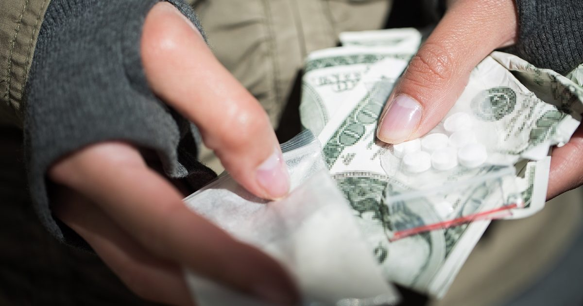 drug trafficking, crime, addiction and sale concept - close up of addict hands with drugs and money. (Syda Productions/Shutterstock)