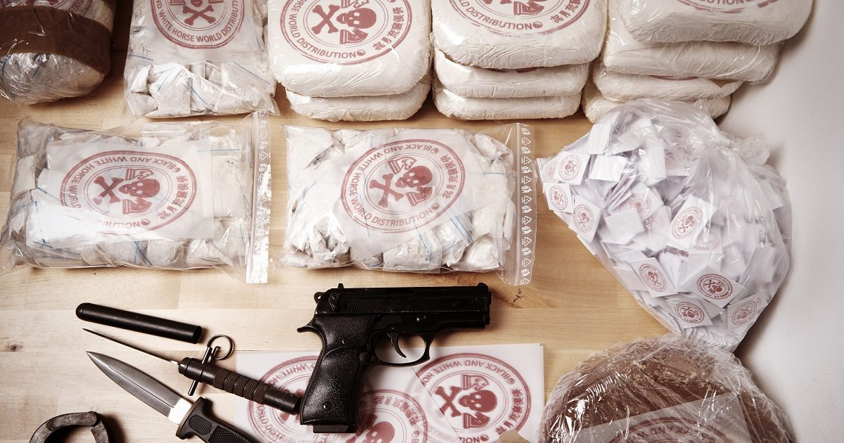Drug packages, raw opium, drug dozens and weapons seized by police. (Couperfield/Shutterstock)