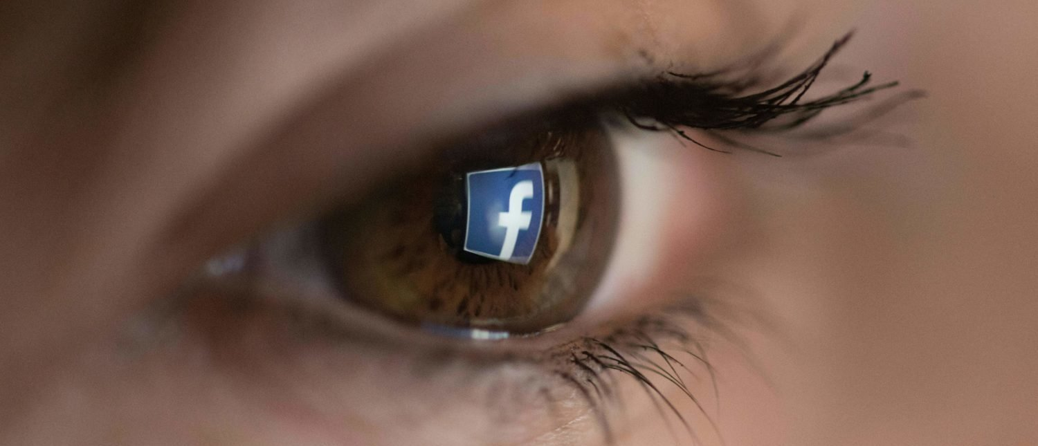 An illustration picture taken on March 22, 2018 in Paris shows a close-up of the Facebook logo in the eye of an AFP staff member posing while she looks at a flipped logo of Facebook. (Photo: CHRISTOPHE SIMON/AFP/Getty Images)
