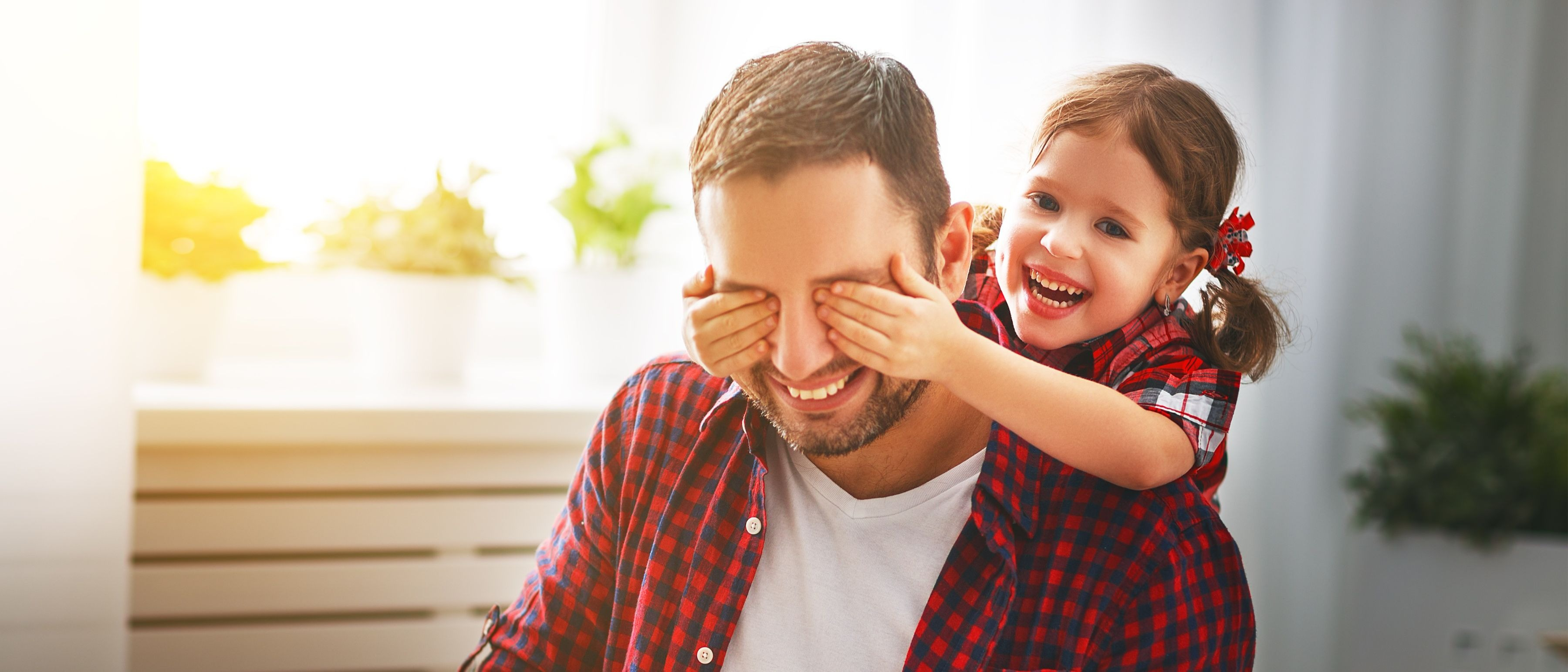 Father's day. A happy family - daughter hugs dad and laughs on a holiday. (Shutterstock)