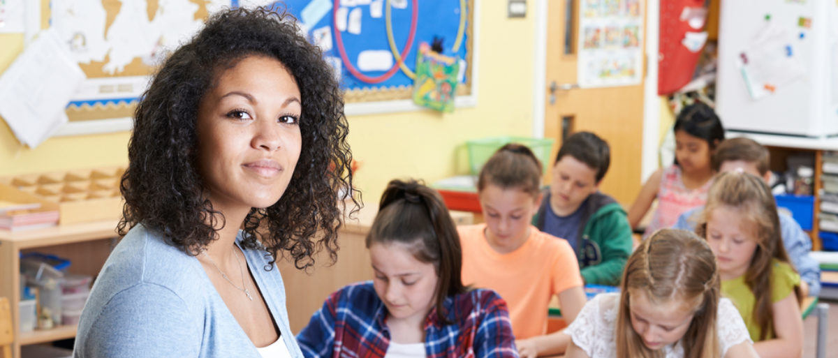 A female teacher stands in front of a classroom. (Shutterstock/SpeedKingz)