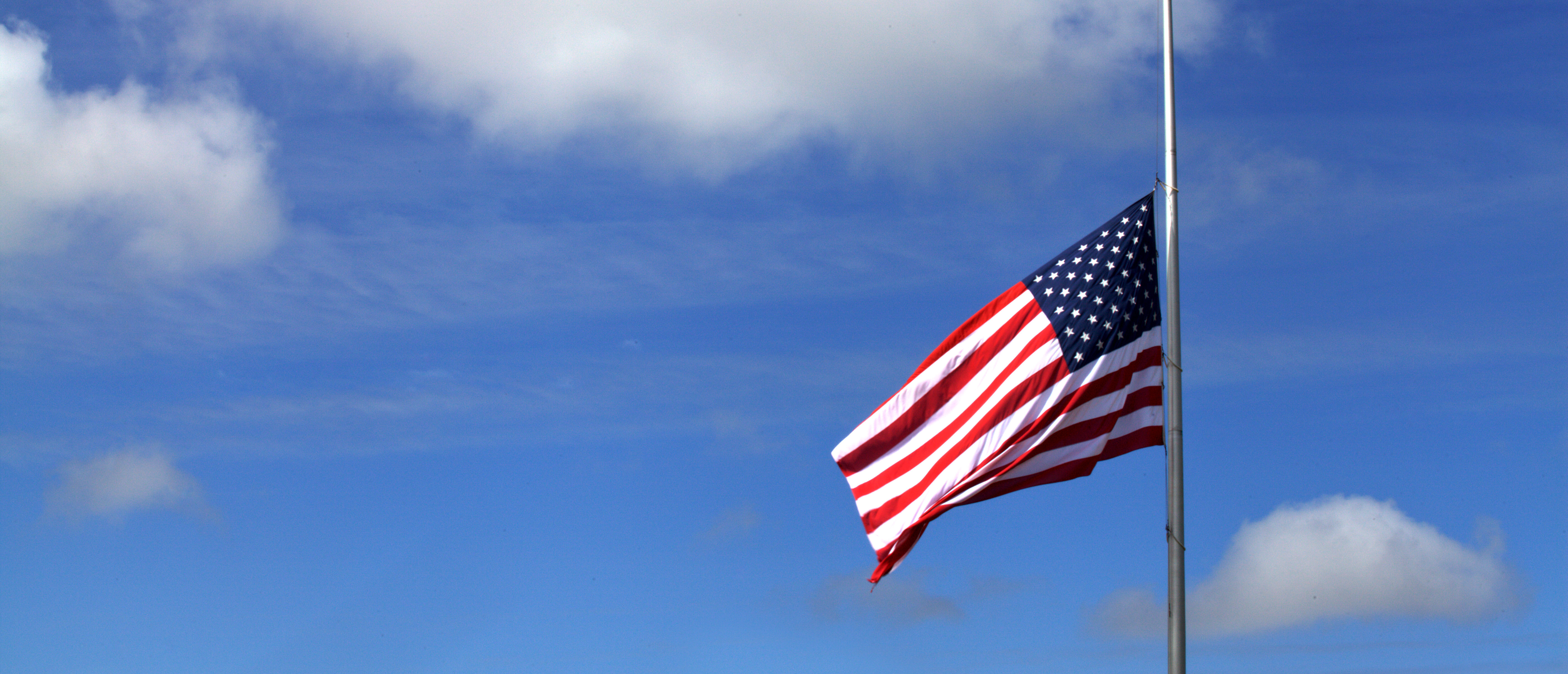 The American flag at half mast. Shutterstock)