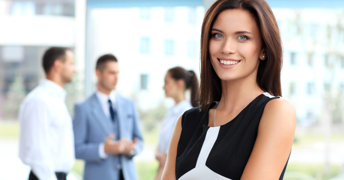 Face of beautiful woman on the background of business people Shutterstock/ OPOLJA