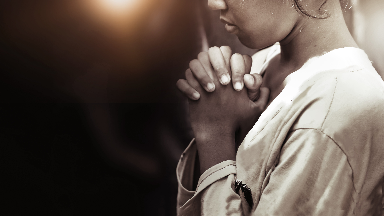 A girl praying. (Shutterstock)