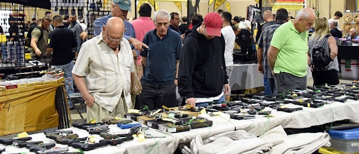 Gun enthusiasts attend the South Florida Gun Show at Dade County Youth Fairgrounds in Miami, Florida, on February 17, 2018. The gun show started three days after a mass shooting 30 miles (48kms) away at the Marjory Douglas High School in Parkland, Florida. Vendors said they were expecting a big turnout and sales, and because of the shooting there will be a panic regarding gun restrictions and new laws that could be put in place. Vendor Domingo Martin said he brought his entire stock of of 42 AR-15's, adding that he is not the only one selling the unit at the weekend show. / AFP PHOTO / Michele Eve Sandberg