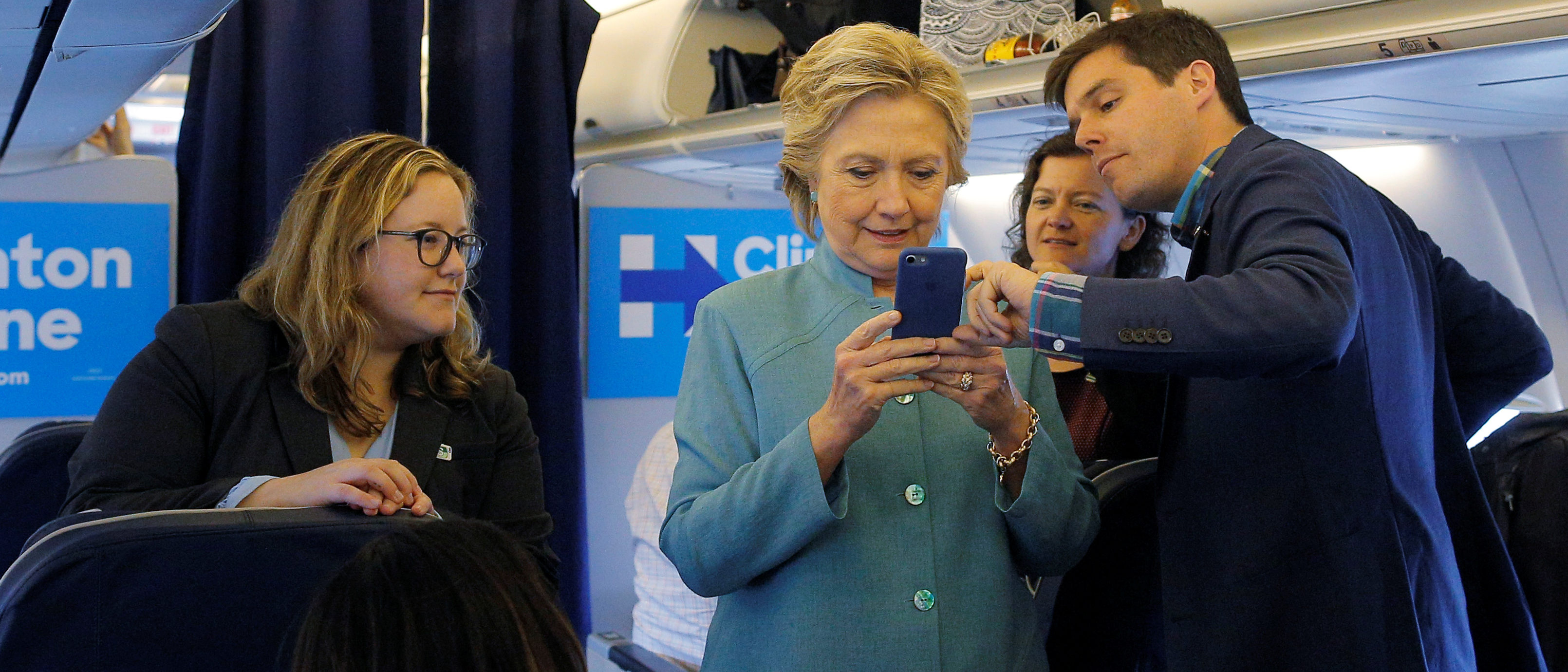 FILE -- Democratic presidential nominee Hillary Clinton looks at traveling press secretary Nick Merrill's mobile phone onboard her campaign plane in Ft. Lauderdale, Florida, November 5, 2016.  REUTERS/Brian Snyder