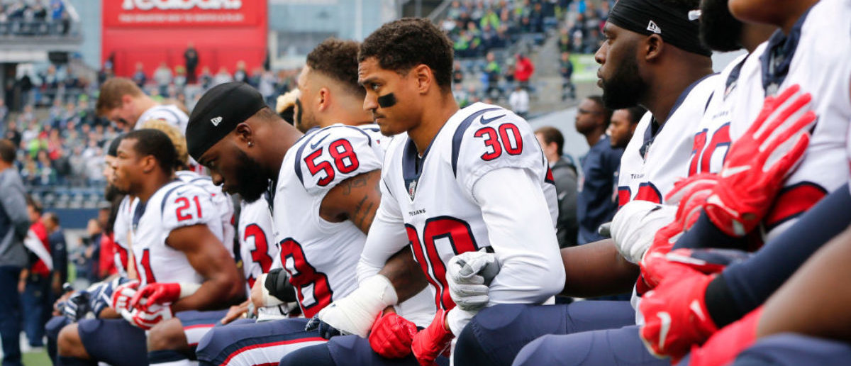 """SEATTLE, WA - OCTOBER 29: Members of the Houston Texans, including Kevin Johnson #30 and Lamarr Houston #58, kneel during the national anthem before the game at CenturyLink Field on October 29, 2017 in Seattle, Washington. During a meeting of NFL owners earlier in October, Houston Texans owner Bob McNair said """"we can't have the inmates running the prison,"""" referring to player demonstrations during the national anthem. (Photo by Jonathan Ferrey/Getty Images)"""