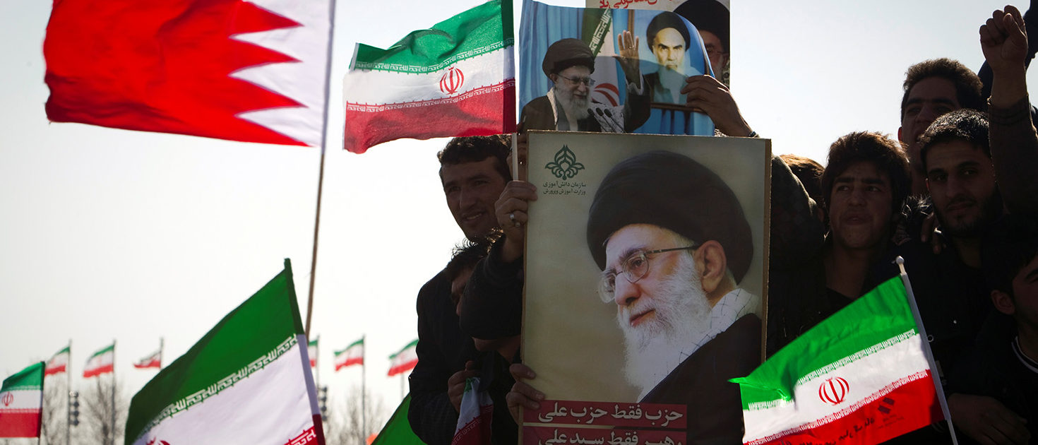 Demonstrators wave Iran's and Bahrain's flags as they hold pictures of Supreme Leader Ayatollah Ali Khamenei during a ceremony to mark the 33rd anniversary of the Islamic Revolution, in Tehran's Azadi square February 11, 2012.  REUTERS/Raheb Homavandi/File Photo