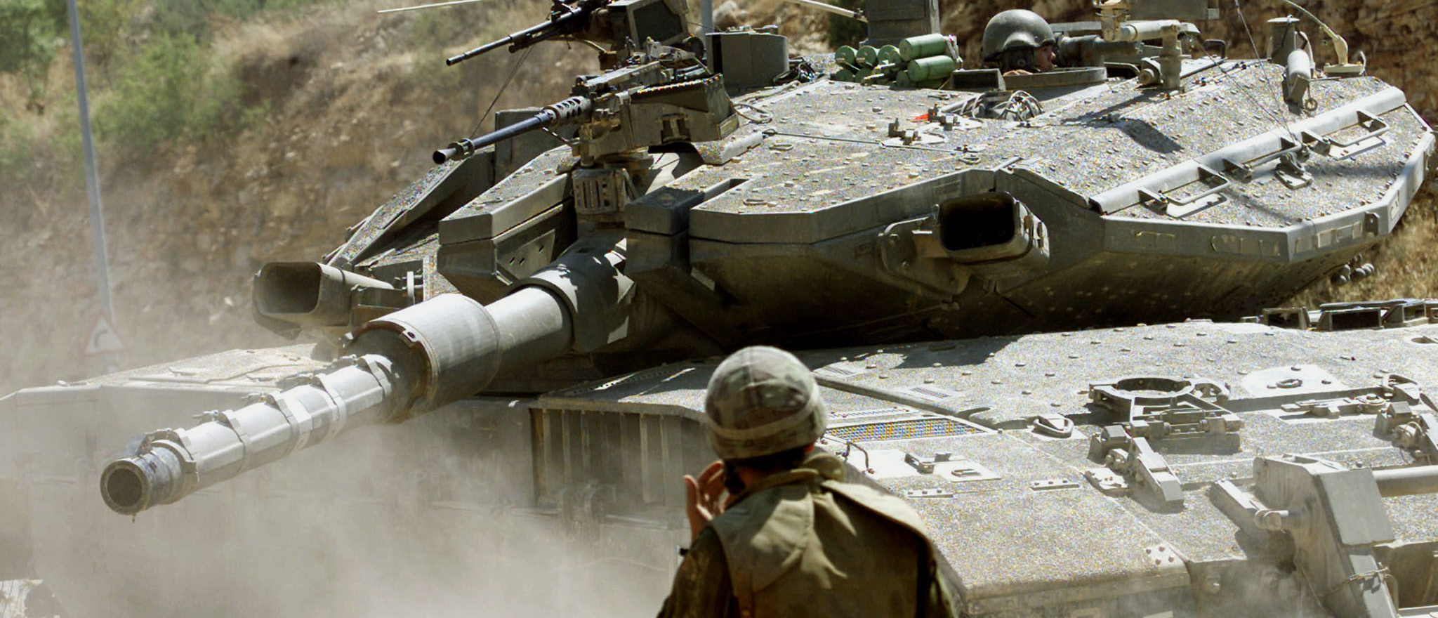 An Israeli soldier guides a Merkava tank into position outskirts of El Hader, 15 km south of Jerusalem June 23, 2002. Israeli armour rumbled into another Palestinian city on Sunday and the army said it was calling up a brigade of reservists under emergency mobilization orders as part of what it was described as a war against terrorism. REUTERS/Gil Cohen Magen YB/CLH/ - RP3DRIAVMEAA