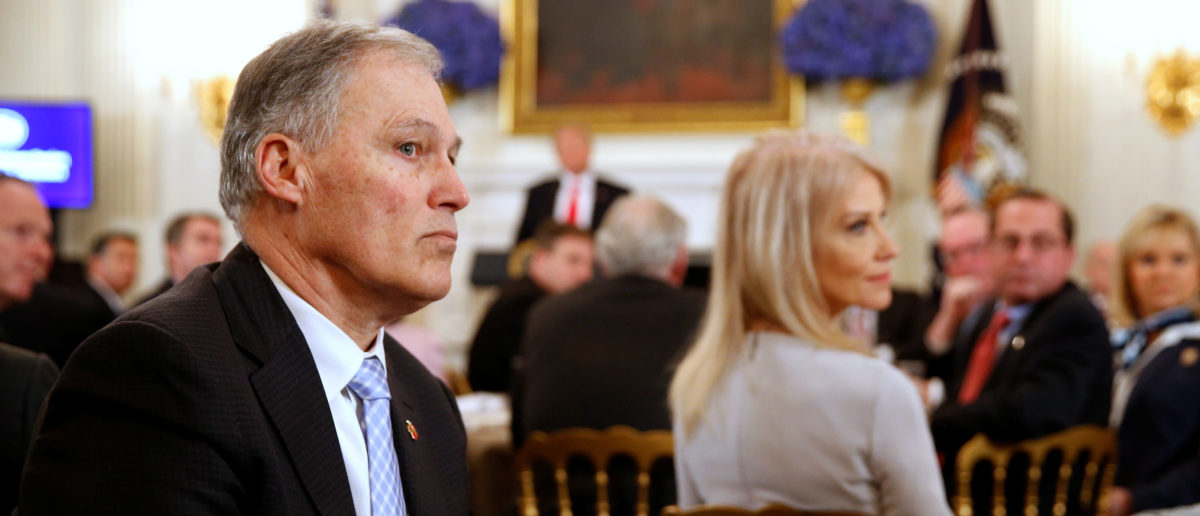 Washington State Governor Jay Inslee (L) listens to participants as U.S. President Donald Trump holds a discussion about school shootings with state governors from around the country at the White House in Washington, U.S. February 26, 2018. REUTERS/Jonathan Ernst
