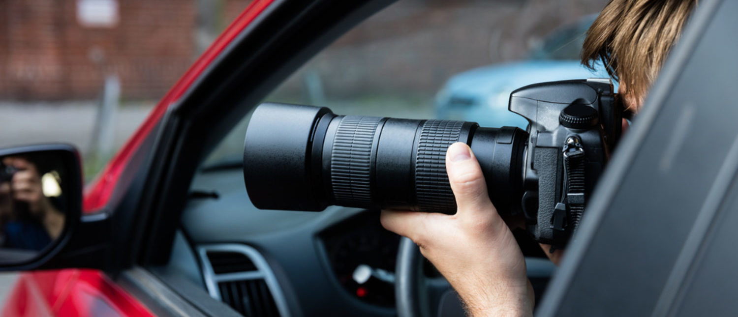 Man sitting inside car snapping photos of people passing by. [Shutterstock - Andrey_Popov]