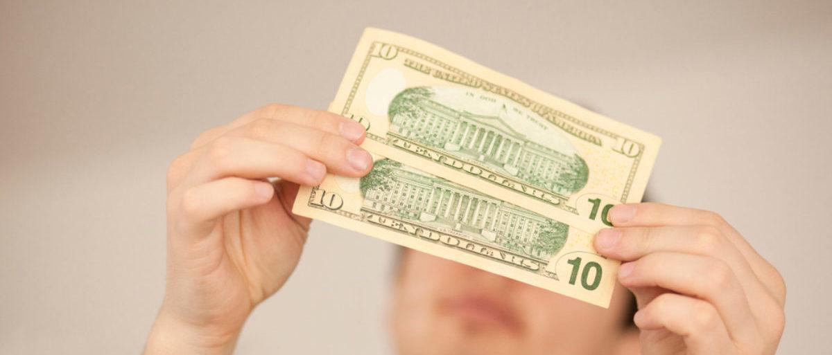 A man examines two ten-dollar bills. (Shutterstock/Blue_Deep)