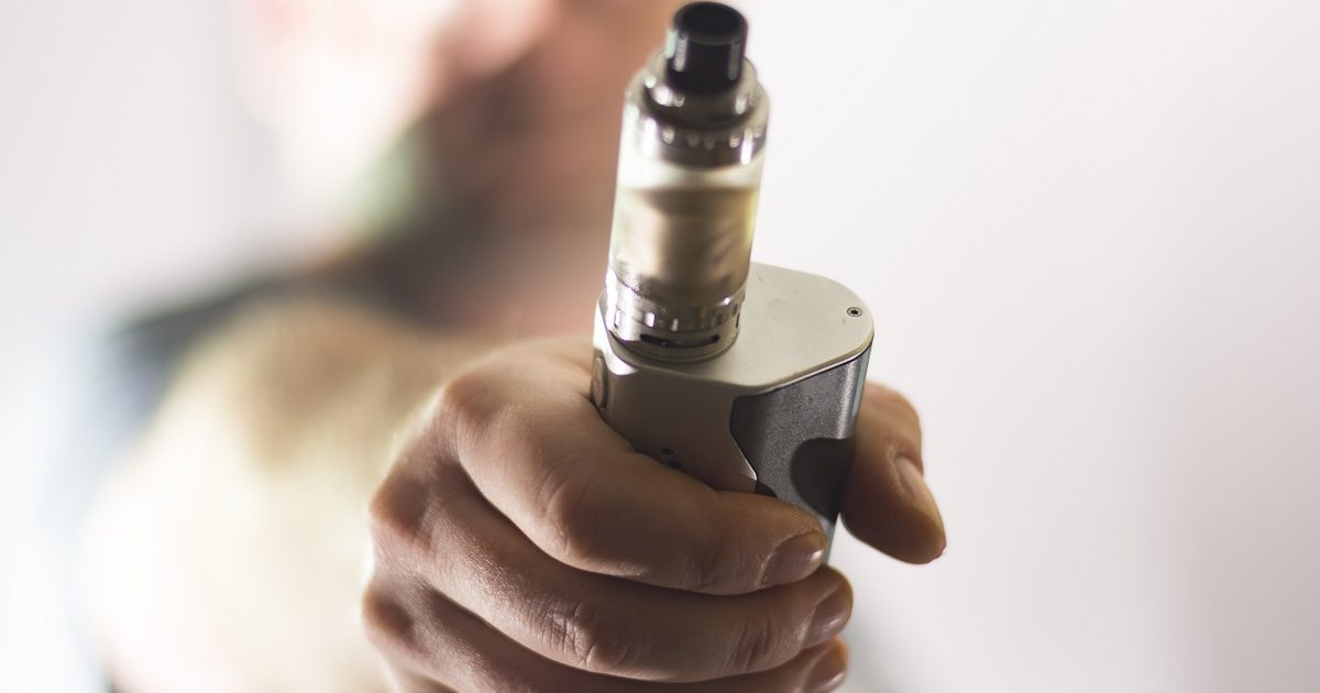 e cigarette on man hand blurred background composition photograph. (FlamencodiabloPhotography/Shutterstock)
