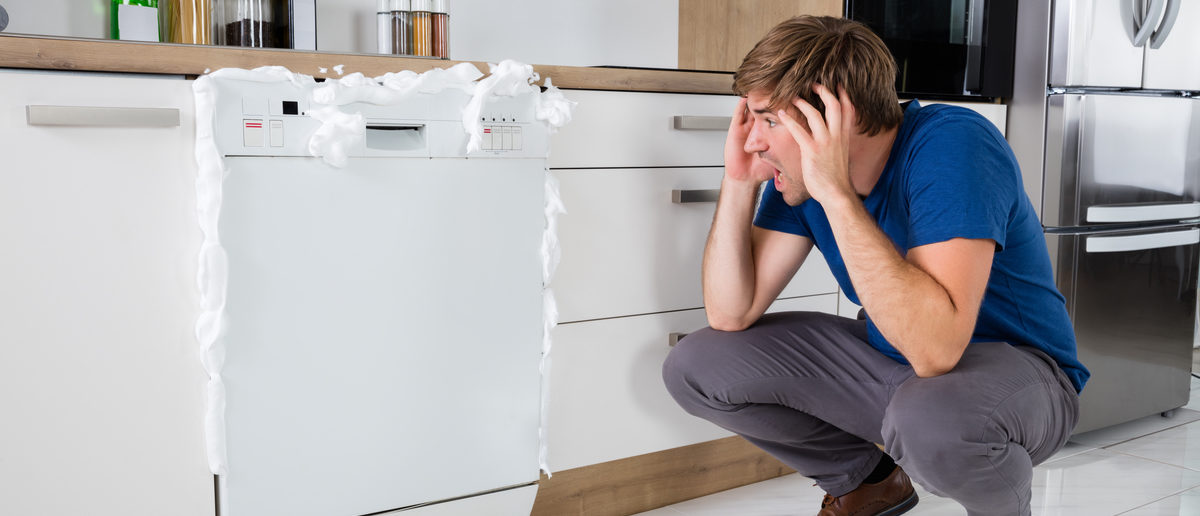Young Man Shocked On Seeing Foam Coming Out Of Dishwasher At Home. (Shutterstock/Andrey_Popov) | Petition Says DOE Makes Dishwashers Worse