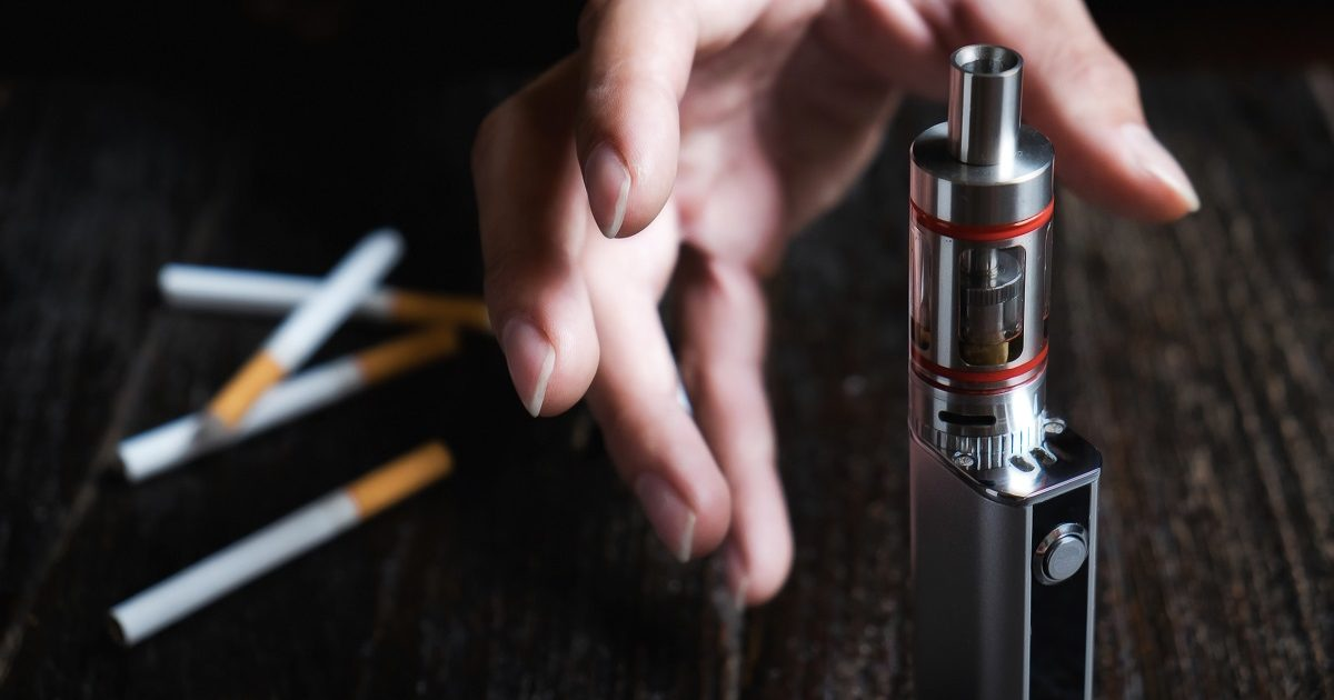 Close up of man hand holding electronic cigarette try to stop smoking cigarette. Concept of tobacco day. (qoppi/Shutterstock)