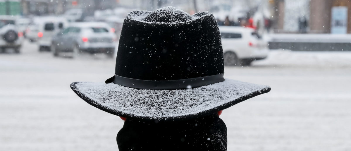 A man waits before crossing a street amid a snow flurry in central Kiev