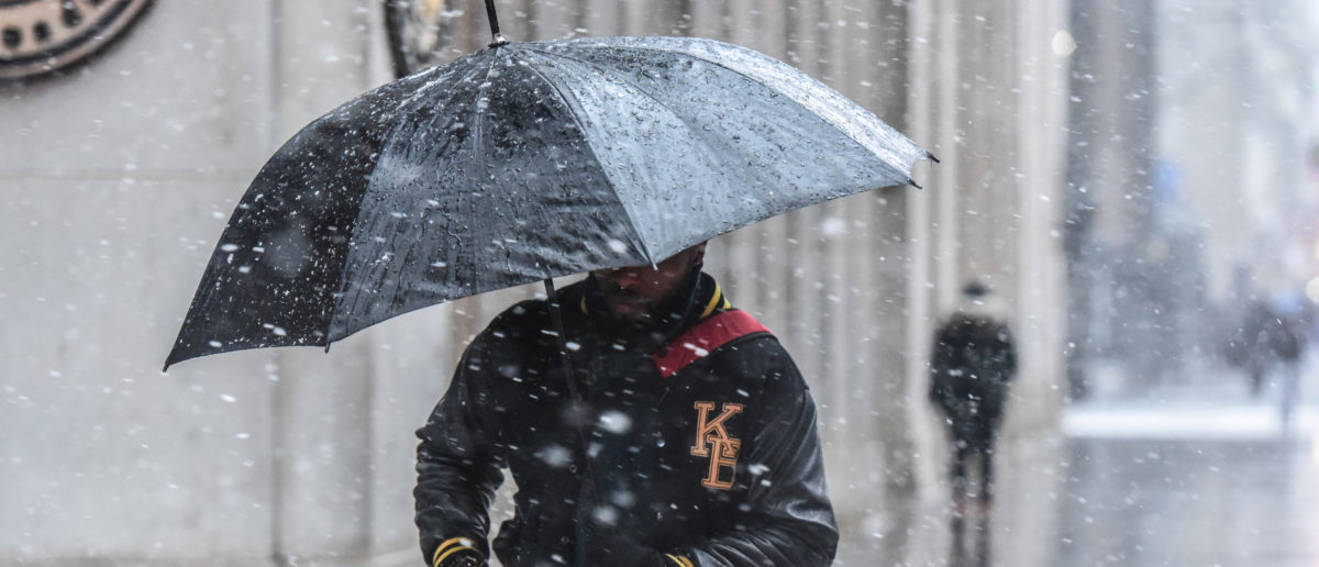 A man carries an umbrella through the snow during a nor'easter storm in New York City