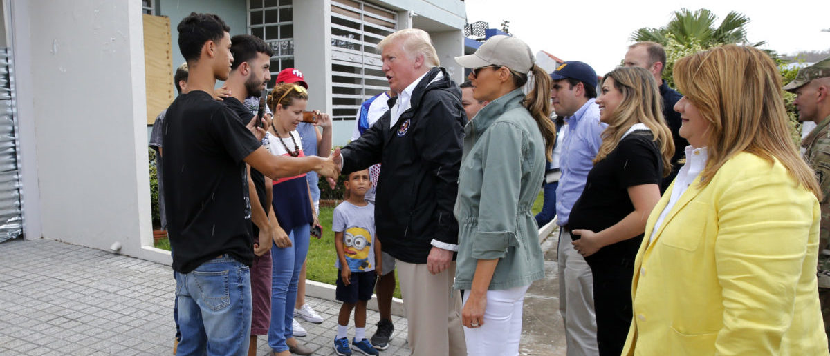 U.S. President Donald Trump talks with residents as first lady Melania Trump (C) and U.S. Rep and Resident Commissioner of Puerto Rico Jenniffer Gonzalez (R) look on as the president visits areas damaged by Hurricane Maria in Guaynabo, Puerto Rico, U.S., October 3, 2017. REUTERS/Jonathan Ernst