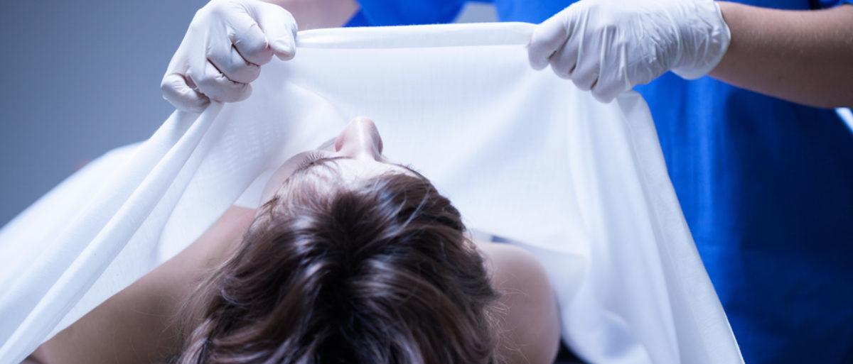 A mortician covers a dead body. (Shutterstock/Photographee.eu)
