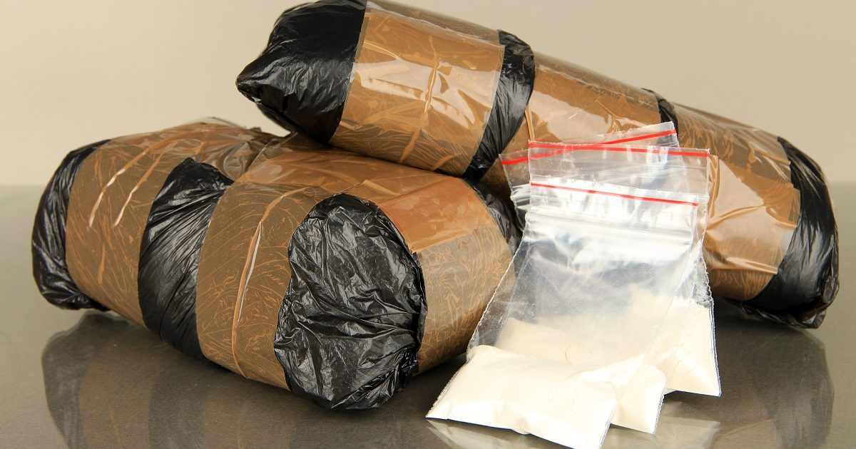 Packages of narcotics on gray background. (Africa Studio/Shutterstock)
