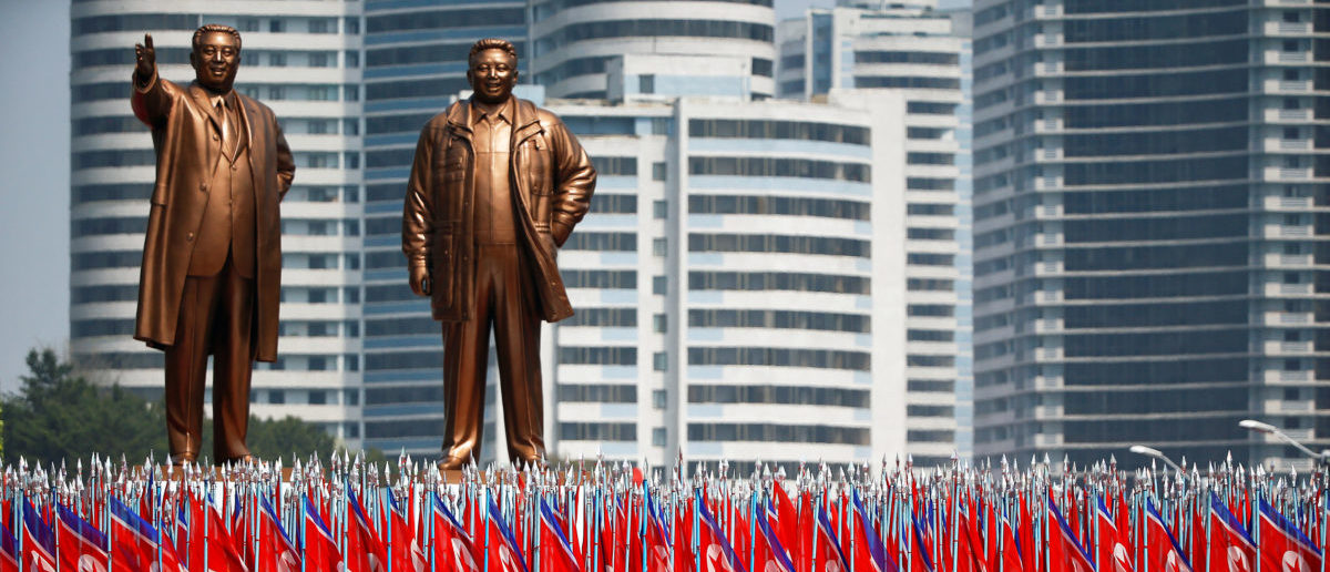 "People carry flags in front of statues of North Korea founder Kim Il Sung (L) and late leader Kim Jong Il during a military parade marking the 105th birth anniversary Kim Il Sung, in Pyongyang April 15, 2017. The men carrying flags are wearing North Korean university uniforms. The float containing the statues is often marks the start of a section of the parade led by people chosen to represent ordinary citizens, as opposed to soldiers or military equipment. Once the parade is over, and the float has completed its official function, a large white sheet is placed over each statue in order to preserve the ""Supreme Dignity"" of each figure as the float meanders its way back through the city amid normal traffic.  REUTERS/Damir Sagolj"