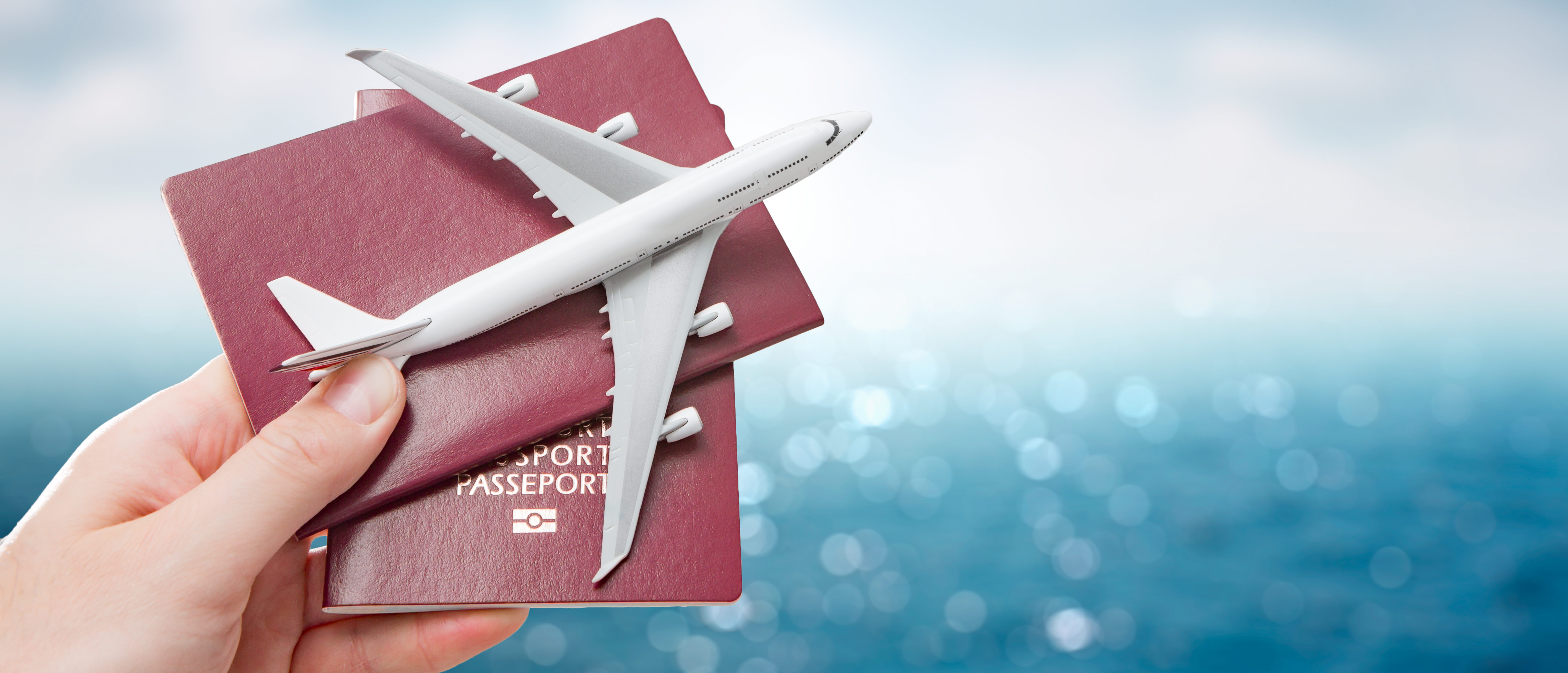 Someone holds a passport and an airplane in their hand. (Shutterstock)