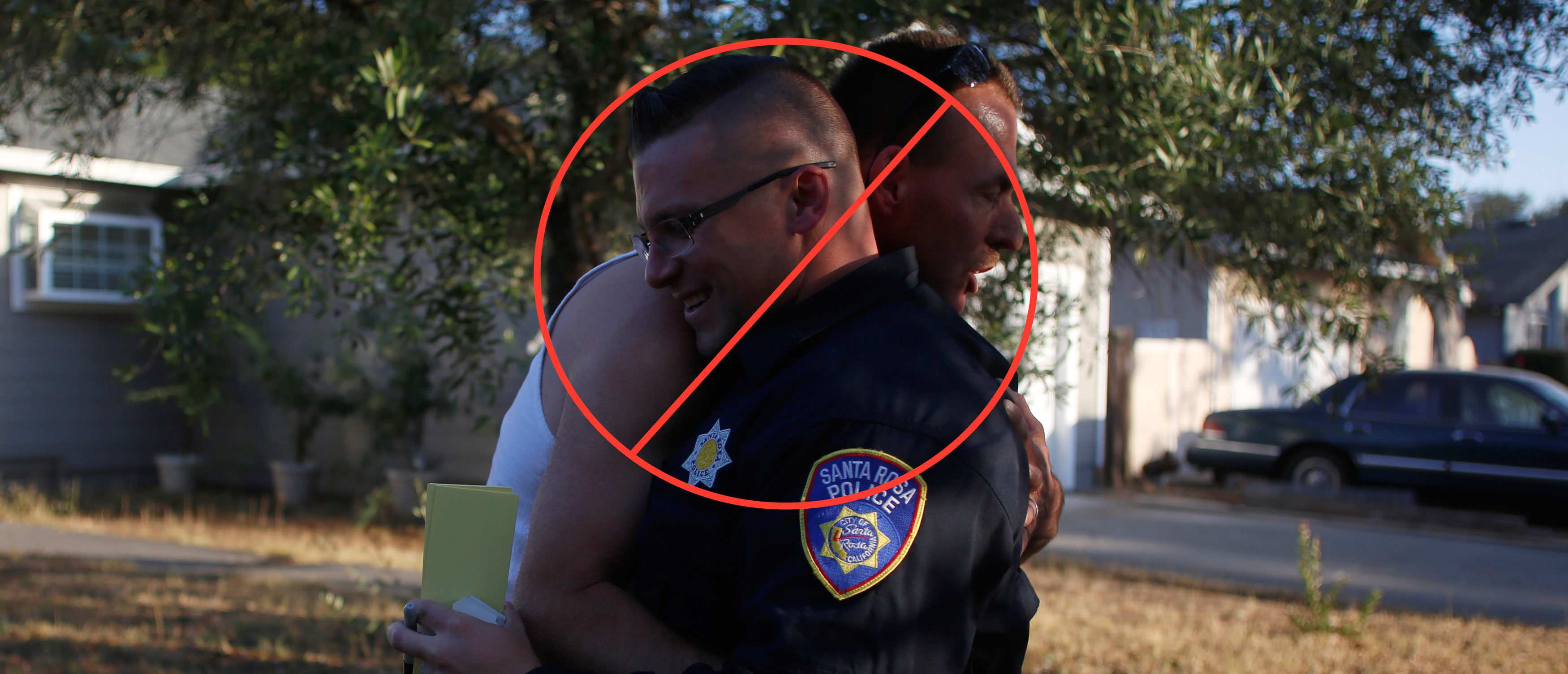 Calvin Sanders hugs Santa Rosa police officer Travis Dunn while receiving a pass that allows him to come and go from the evacuation zone he lives in after a wildfire tore through adjacent streets in Santa Rosa, California, U.S. October 15, 2017. REUTERS/Jim Urquhart