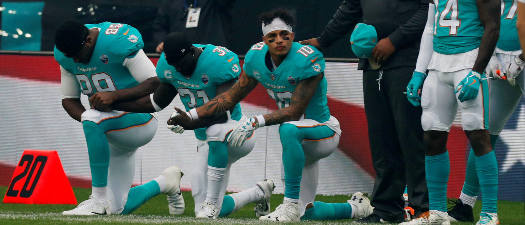 Miami Dolphins players kneel during the U.S. national anthem before a game against the New Orleans Saints at Wembley Stadium in London, October 1, 2017. Action Images via Reuters/Paul Childs