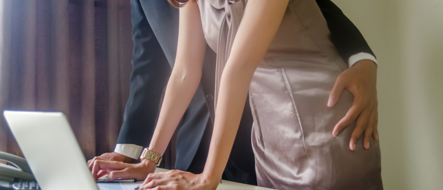 A co-worker inappropriately touching a female colleague on the hip. [Shutterstock - 0306PAT]