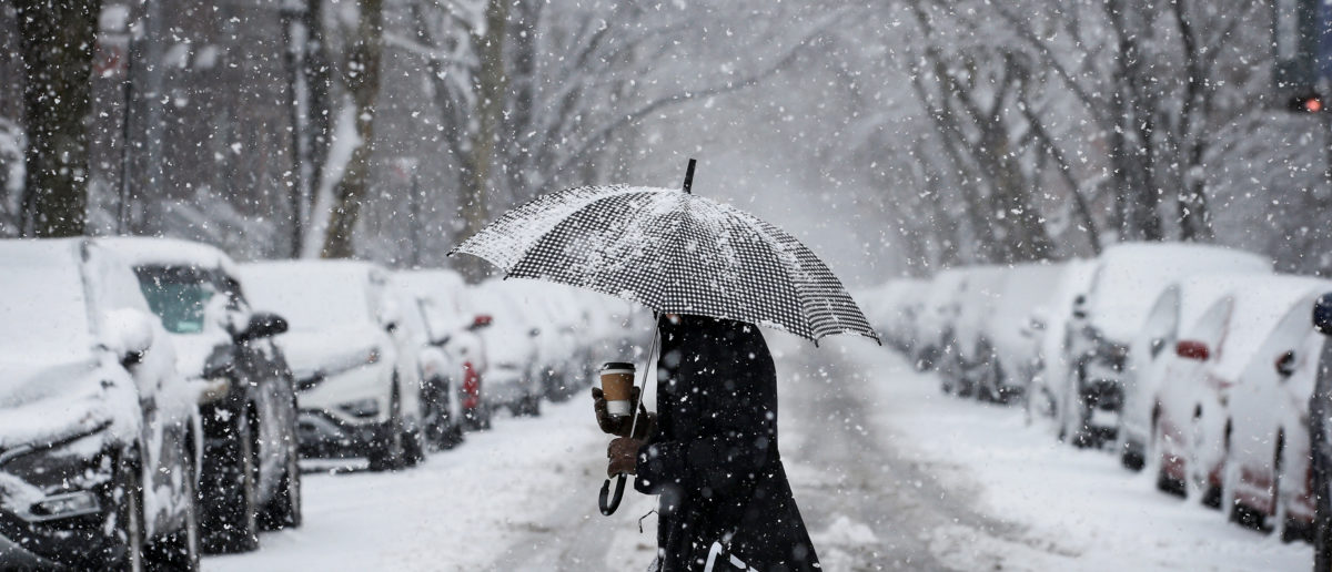 A woman walks in the snow during a winter nor'easter storm in the Brooklyn borough of New York, U.S., March 21, 2018. REUTERS/Brendan McDermid - RC175385BDD0