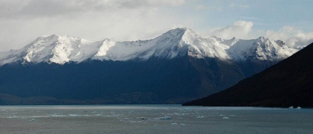 Panoramic view of the snow-capped mountains and the Argentino lake, at Parque Nacional Los Glaciares near El Calafate, in the Argentine province of Santa Cruz, on March 12, 2018.  An arch of ice formed at the tip of the Perito Moreno, between the glacier and the shore of Argentino lake collapsed into the water overnight. A natural display that happens just once every several years. Such arches form roughly every two to four years, when the glacier forms a dam of ice that cuts off the flow of water around it into the lake -- until the water breaks through, opening up a steadily wider tunnel that eventually becomes a narrow arch and then collapses.  / AFP PHOTO / WALTER DIAZ | Weird Orange Snowstorms Hit Europe