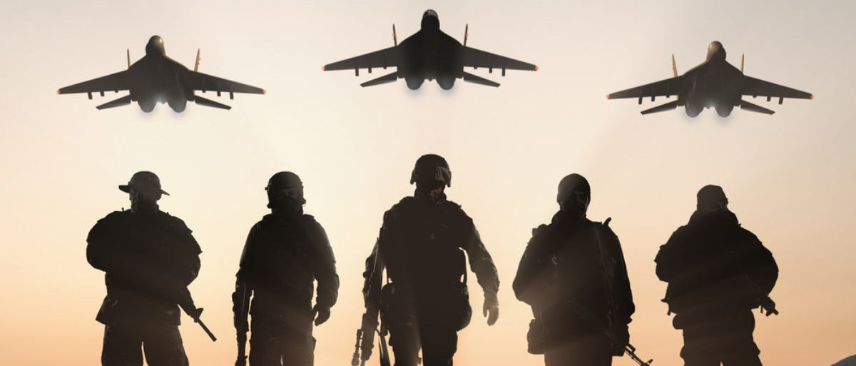 Soldiers stand with aircrafts above them. (Shutterstock/BPTU)