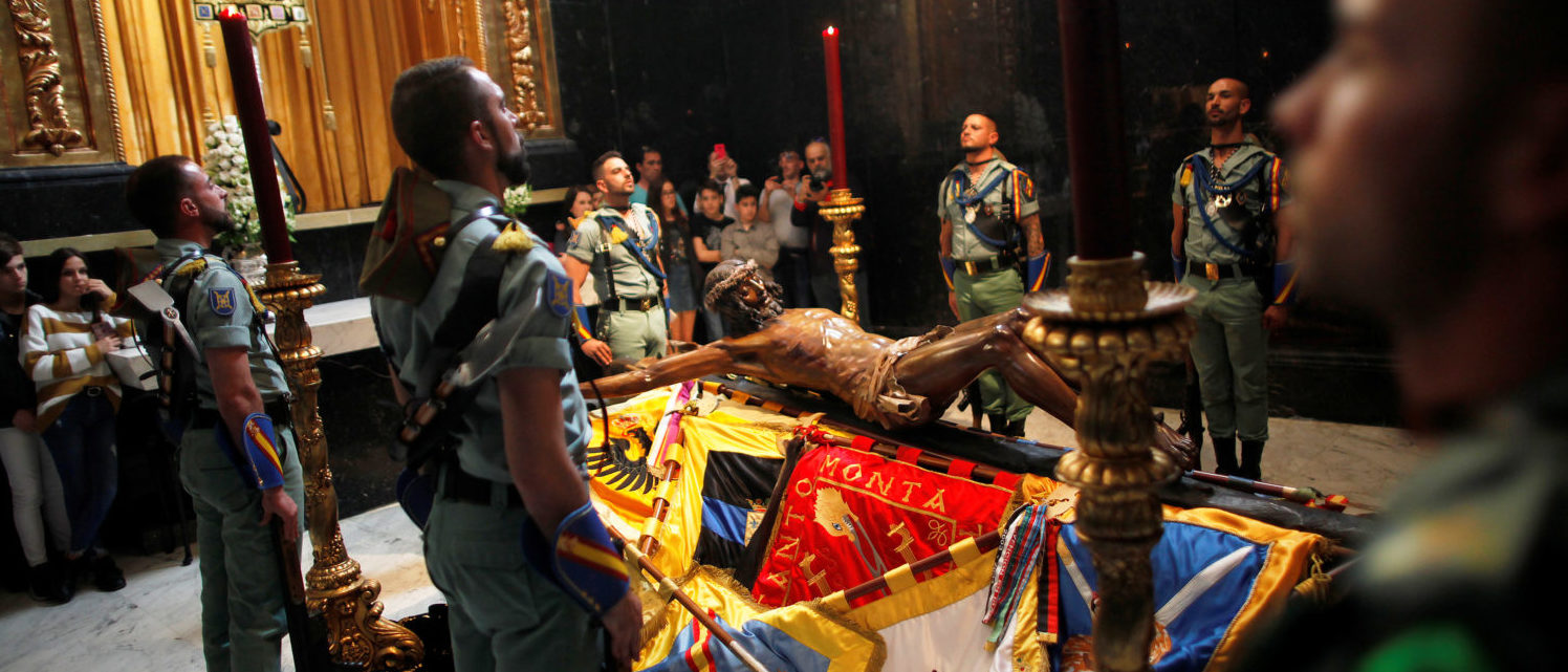 Spanish legionnaires stand at attention during a change of honor guard near the statue of the Christ of Mena brotherhood inside a church during Holy Week in Malaga, southern Spain, March 26, 2018. REUTERS/Jon Nazca   Spain Honors Christ With Half Mast Flags
