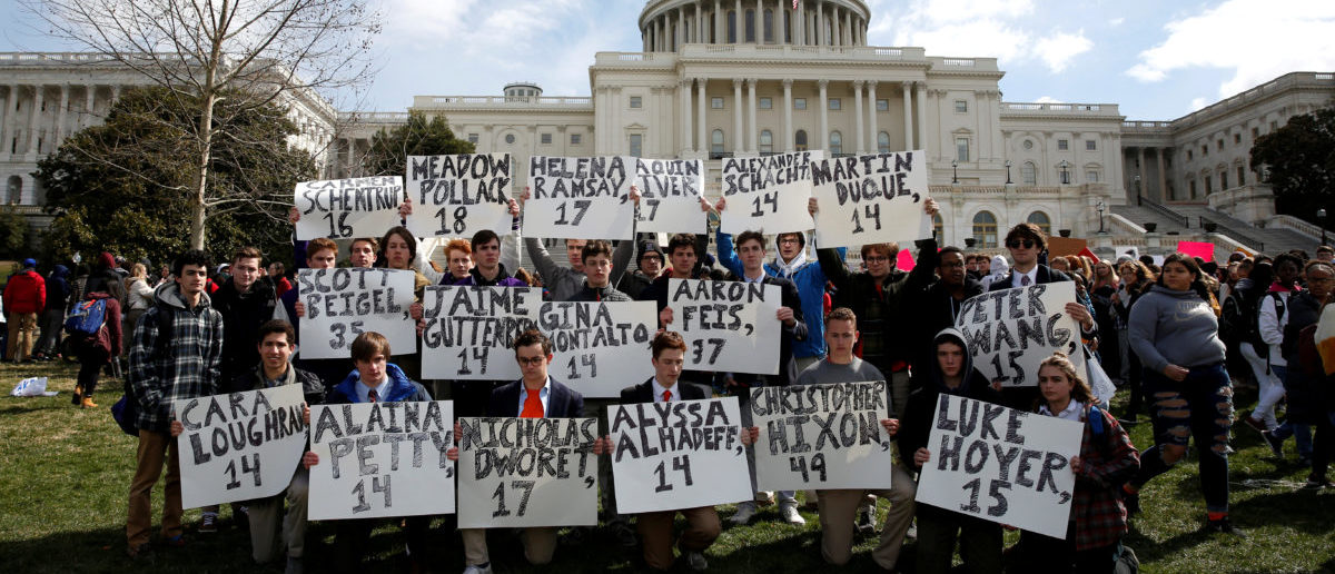 Students from Gonzaga College High School in Washington, DC, hold up signs with the names of those killed in the Parkland, Florida, school shooting during a protest for stricter gun control during a walkout by students at the U.S. Capitol in Washington, U.S., March 14, 2018. REUTERS/Joshua Roberts