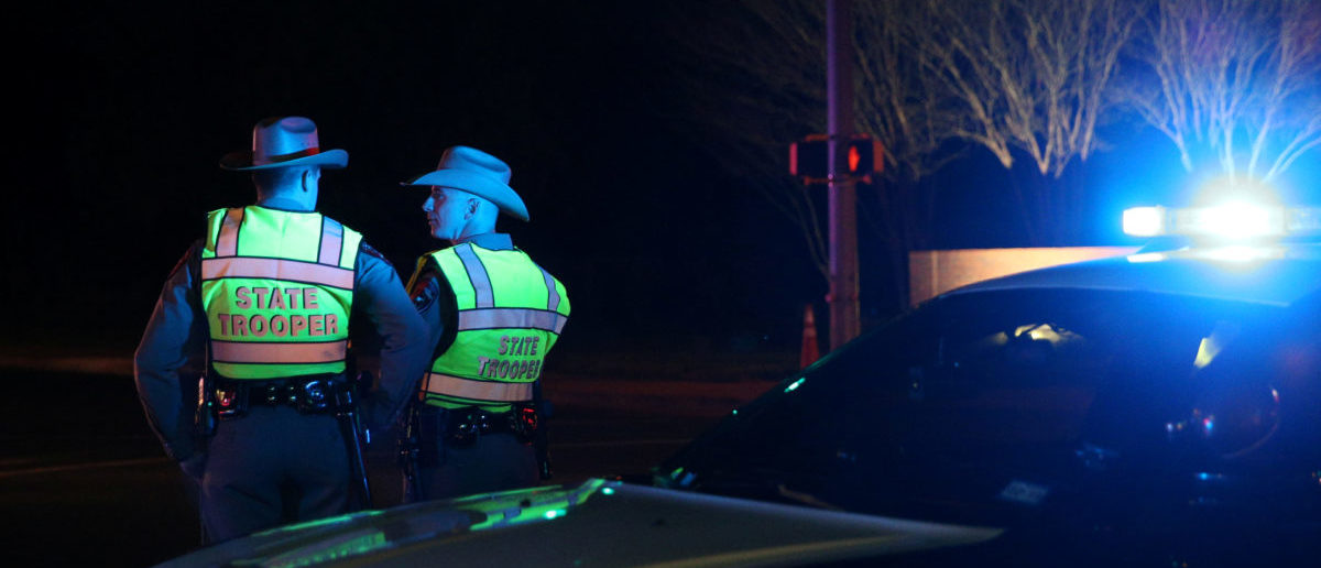 Texas state troopers keep watch at a checkpoint as nearby law enforcement personnel investigate an incident that they said involved an incendiary device in the 9800 block of Brodie Lane in Austin, Texas, U.S., March 20, 2018. REUTERS/Loren Elliott