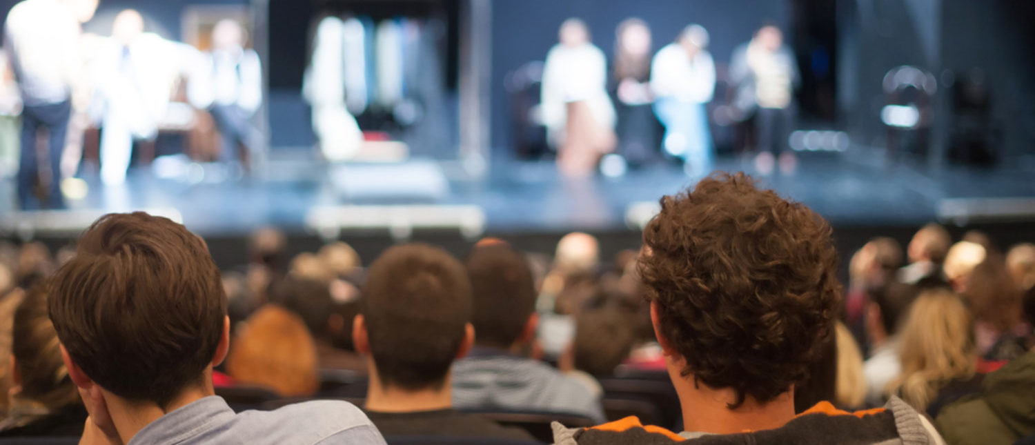 Audience sitting in a theater watching a play. [Shutterstock - aerogondo2]