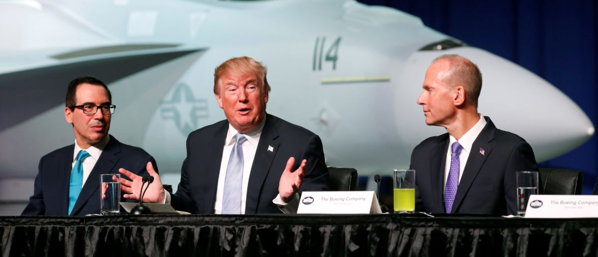 U.S. President Donald Trump sits between Treasury Secretary Steve Mnuchin (L) and Boeing Chairman and CEO Dennis Muilenburg (R) during a round table at Boeing in St. Louis, Missouri, U.S. March 14, 2018. REUTERS/Kevin Lamarque