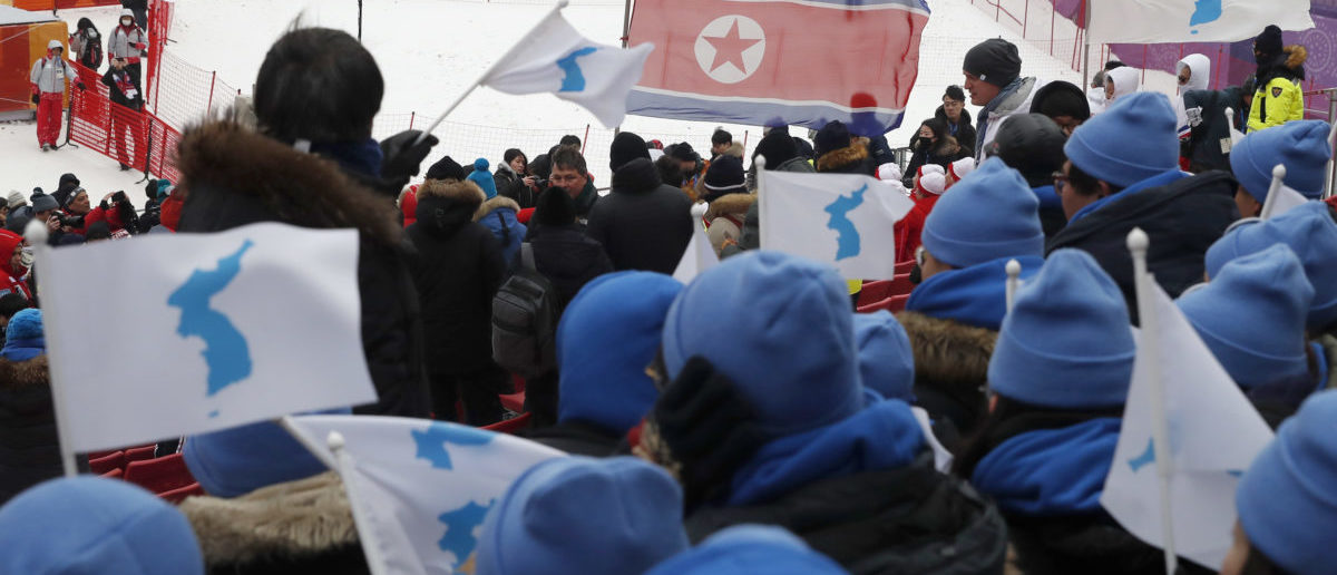 Alpine Skiing – Pyeongchang 2018 Winter Olympics – Women's Slalom – Yongpyong Alpine Centre - Pyeongchang, South Korea – February 14, 2018 - South Koreans cheering in favour of a unified Korea are seen with a North Korean flag in the background. REUTERS/Mike Segar -