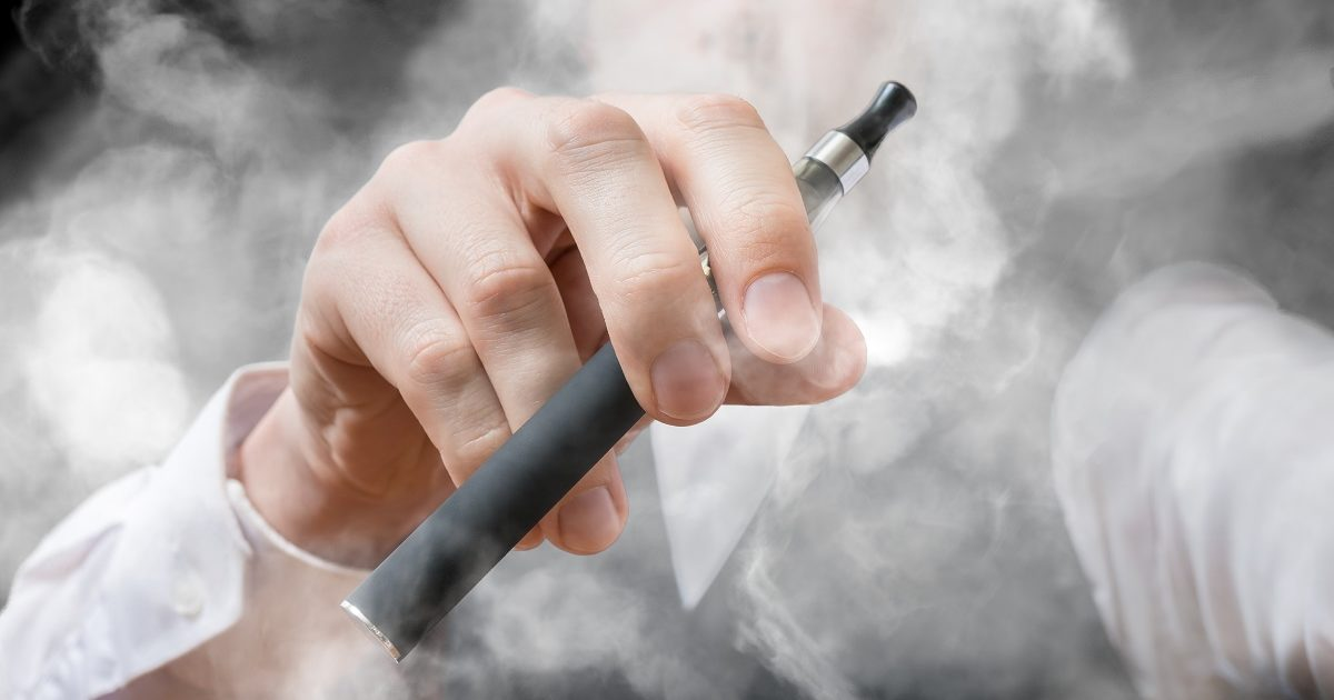 Smoking man holds electronic cigarette in hand. A lot of smoke around. (vchal/Shutterstock)