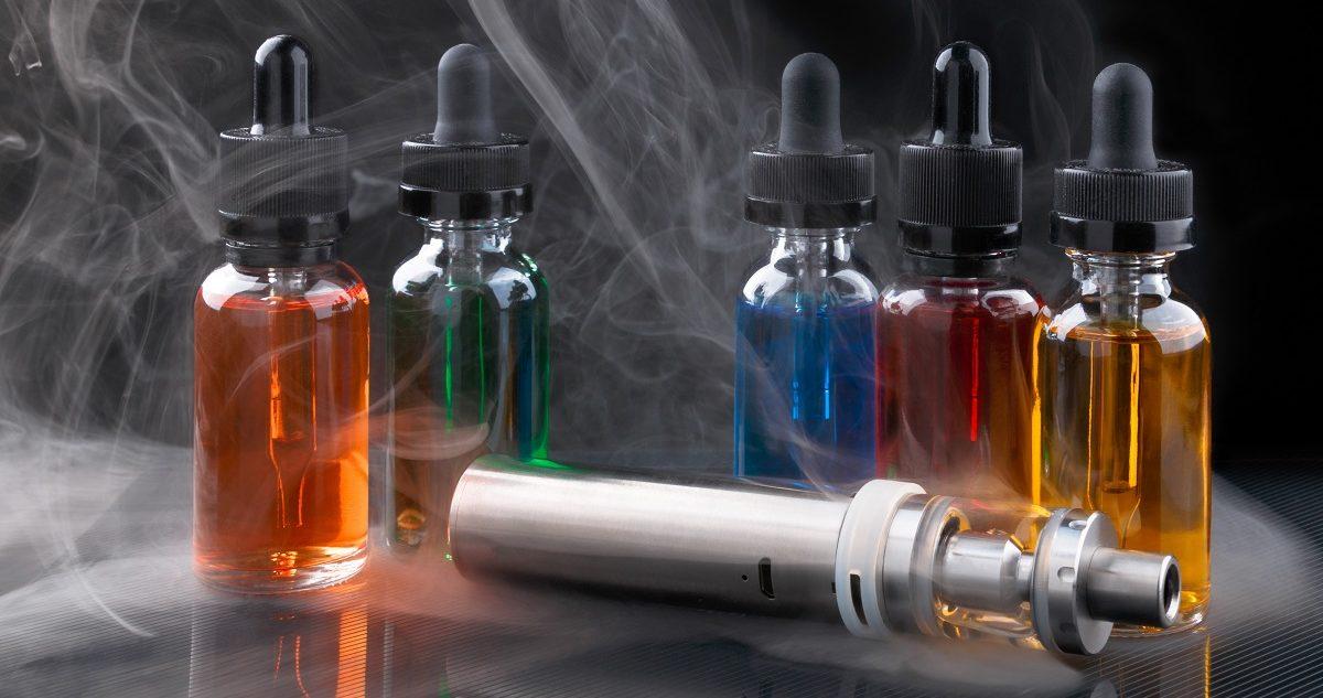 Electronic cigarette and vape liquids within vapor on black background. (MakcouD/Shutterstock)