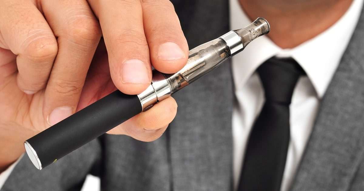 A man is wearing a suit vaping with an electronic cigarette. (nito/Shutterstock)